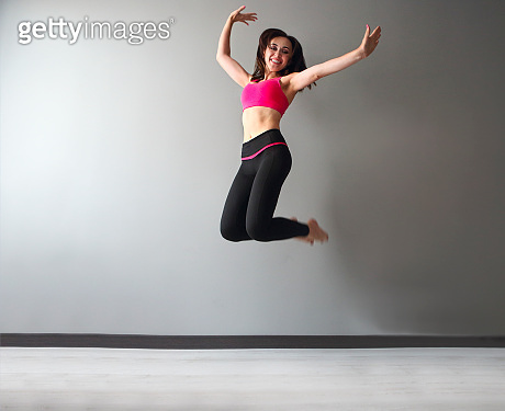 Full length view of athletic young woman in sportswear jumping