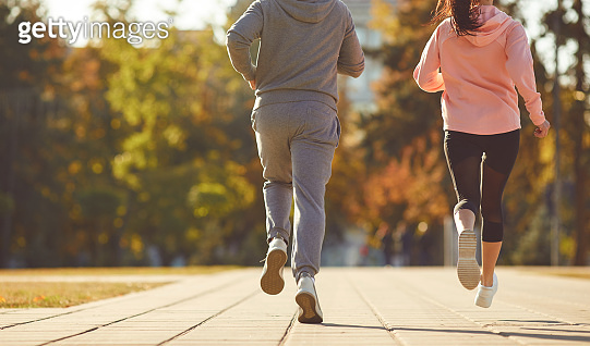 A man and a woman are running along the city street in the morning.