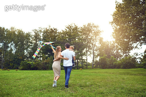 Happy family runs with a kite through the grass in park.
