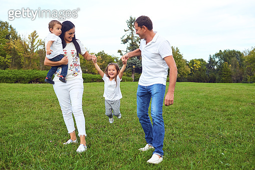 Family with children playing on the grass in the park.