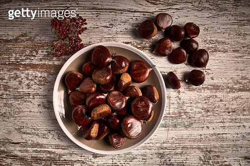 group of tasty chestnuts next to a bowl