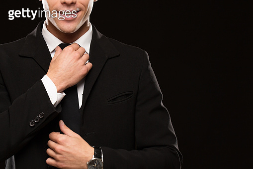 Handsome male security guard in black suit on black background