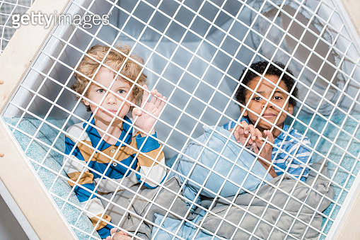 Two preschool boys of African and Caucasian ethnicities relaxing on play area