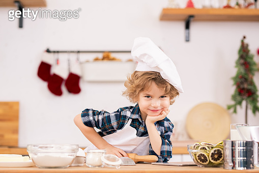 Cute little boy in apron and chef hat holding rolling-pin and looking at you