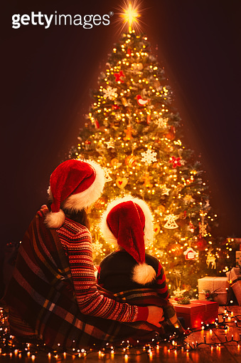 Christmas Family Looking Lighting Xmas Tree, Mother and Child in Red Santa Hats, New Year Night