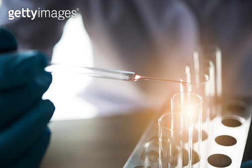 lab technician assistant analyzing a blood sample in test tube at laboratory. Medical, pharmaceutical and scientific research and development concept.