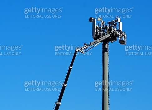 Technicians on an aerial platform does maintenance for upgrade the technologies of a cellular phone repeater tower