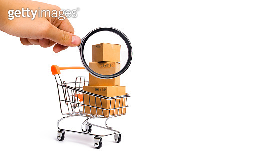 Magnifying glass is looking at the Supermarket cart with boxes, merchandise: the concept of buying and selling goods and services, internet commerce, online shopping, trade and turnover.