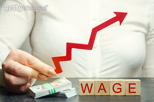 Female hand holds arrow up above word wage. Increase of salary, wage rates. Promotion, career growth. Raising the standard of living. Increase profits and family budget. Wooden blocks
