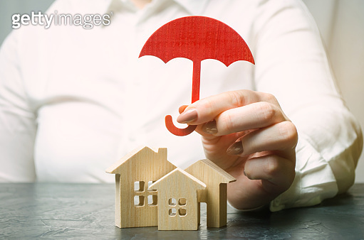Property insurance concept. Protection of home. Housing support. Insurance agent services. Security and safety. Miniature wooden houses.