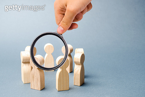 Magnifying glass is looking at people stand in a circle on a gray background. Wooden figures of people. A circle of people. discussion, cooperation, cooperation. teamwork, team spirit. Selective focus