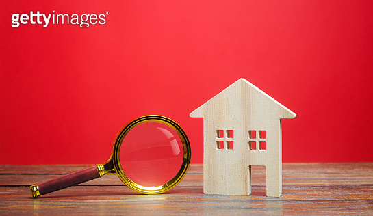 Wooden house and magnifying glass. House searching concept. Home appraisal. Property valuation. Choice of location for the construction. Search for housing, apartments. Real estate. Red background
