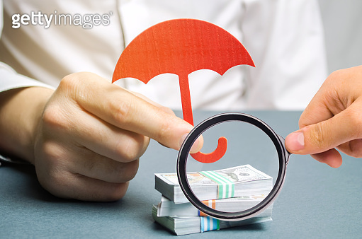An insurance agent holds a red umbrella over dollar bills. Savings protection. Keeping money safe. Investment and capital insurance. The risk of doing business. Corruption losses. Arrest of investors