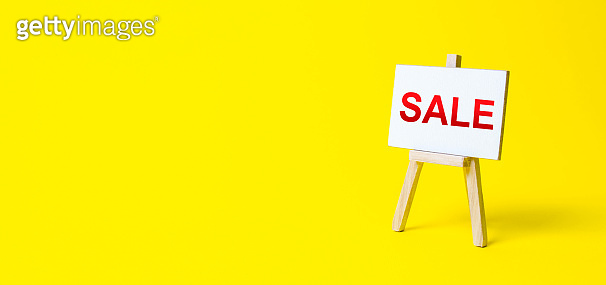Easel sign with the words Sale. Advertising marketing. Discount. Shopping online. Increase sales and attract new customers. Sale of goods and products by attractive prices and promotions.