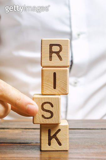 Man removes blocks with the word Risk. The concept of reducing possible risks. Insurance, stability support. Legal protection of business interests. Favorable investment climate. Financial pillow.