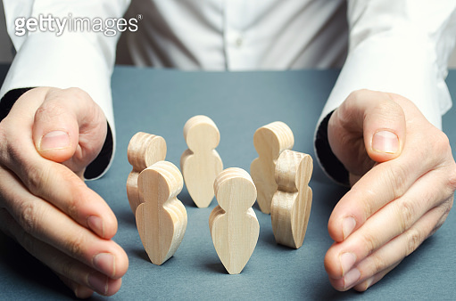A man embraces a circle of human figures. Care and protection, insurance team. Patronage of communities and groups. Creating the conditions for negotiations and probing, cooperation of people.