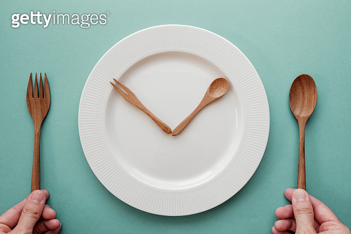 wooden spoon and fork as a clock hands on white plate, Intermittent fasting concept, ketogenic diet, weight loss, skip meal