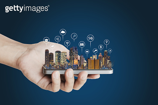 Hand holding mobile smart phone with buildings hologram and technology icons. Smart city, 5g, internet, blockchain technology, and networking technology concept
