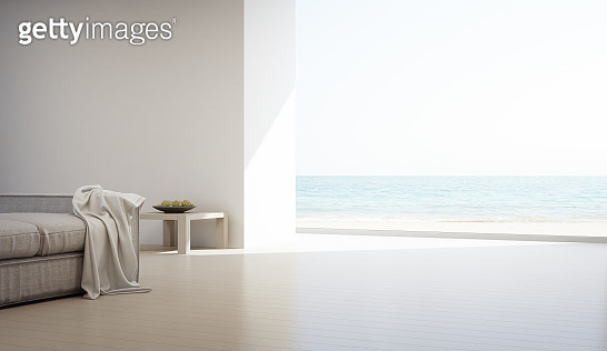 Sea view living room of luxury summer beach house with glass window and wooden floor. Empty white concrete wall background in vacation home or holiday villa.