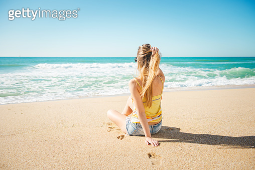 Young beautiful and blond girl sitting and relaxing on the beach