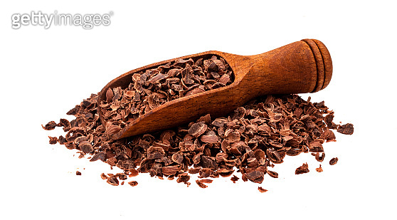 Grated chocolate. Pile of ground chocolate with wooden scoop isolated on white background, closeup