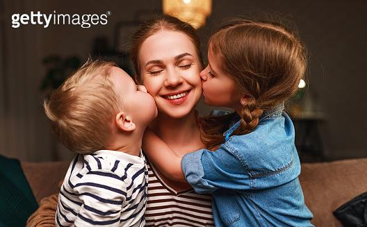 Happy family! Children kisses moms evening before bedtime
