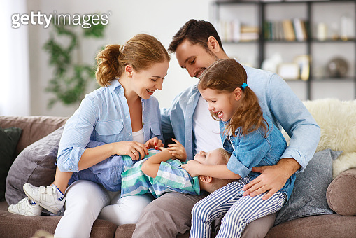 happy family mother father and kids at home on couch
