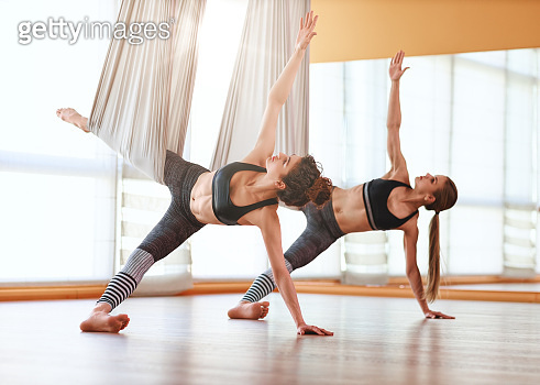group of people engaged in a class of yoga Aero in hammocks antigravity