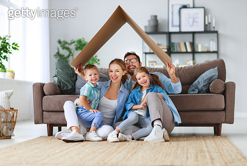 concept of housing and relocation. happy family mother father and kids with roof at home