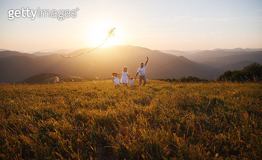 Happy family father,  mother and children launch  kite on nature at sunset