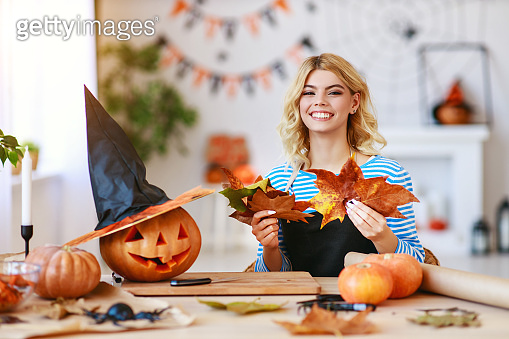 happy girl is cutting  pumpkin and is preparing for holiday Halloween