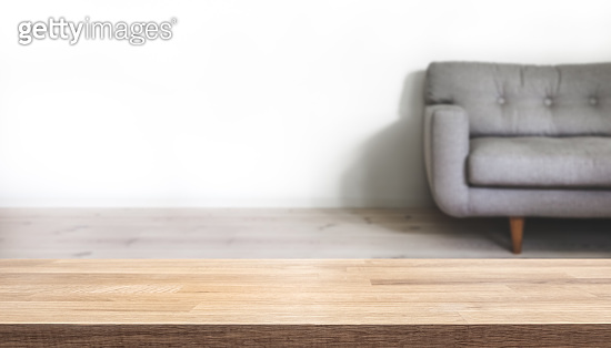 Empty table top with simple home interior with grey couch blurred in the background.