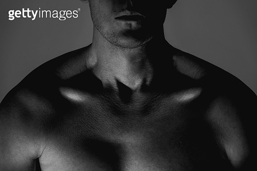Dark close up studio shoot of strong masculine athletic man.