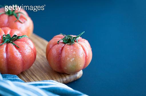Nice fresh farm tomatos. Red tomatos on wooden background. Italian dish ingredient