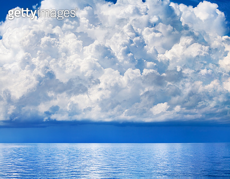 White cumulus clouds over sea close up blue sky background landscape, big fluffy cloud above ocean water panorama, scenic tropical sunny summer day cloudy weather seascape view, cloudscape, copy space