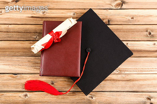 Graduation cap with diploma and book on brown wooden table