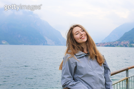 Young happy girl standing near banister, lake Como and Alps mountain in background