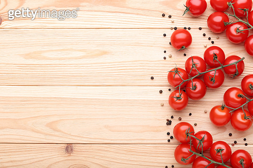 Cherry tomatoes with spices on brown wooden table