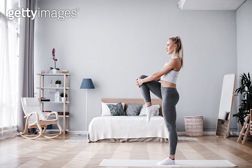 Full length portrait of attractive young woman working out at home, doing pilates exercise on mat.