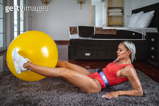 Motivated fitness girl lifting a pilates ball indoors in bedroom