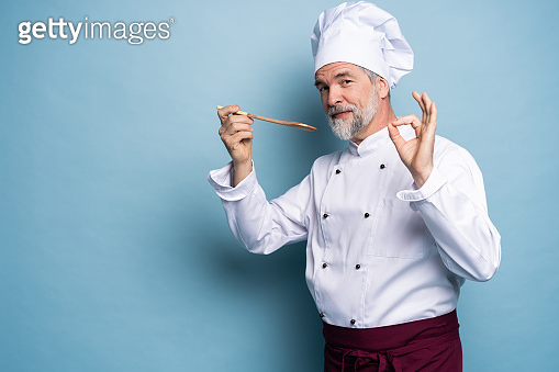 Chef trying meal. Confident mature chef in white uniform trying eating from wooden spoon and standing against blue background.