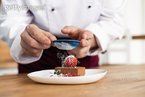 Close up pastry chef decoration delicious dessert dish, serving for customers in bakery, garnishing dessert plate in commercial kitchen.