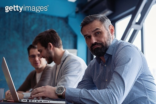 Middle age top manager working at the wood table in modern interior design office. Stylish bearded businessman using laptop on workplace