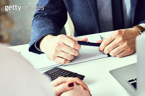 Close up focus on male hand holding ballpoint and listening to colleague or employee. Corporate team training, negotiations, business seminar job interview concept