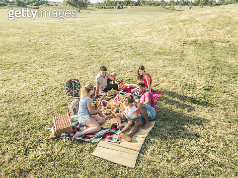 Happy families doing picnic in park outdoor - Young parents having fun with children in summer time eating and playing - Food, weekend lifestyle and friendship concept - Main focus on blond girl face