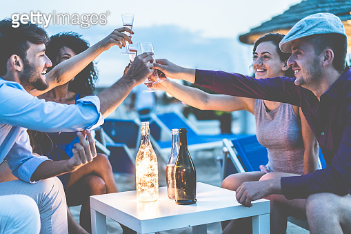 Group of young tourist friends cheering with champagne at beach party - Happy people having fun in summer holidays - Focus on hands glasses - Fun,vacation, summer lifestyle and youth concept