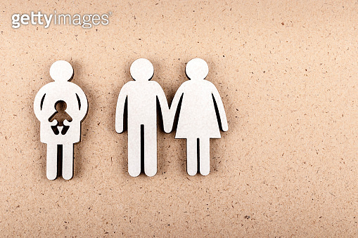Family and couple concept. Wooden figures on brown paper background. Family, pregnancy, abortion or adoption concept.