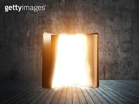 Old open book with magic light and falling on wooden