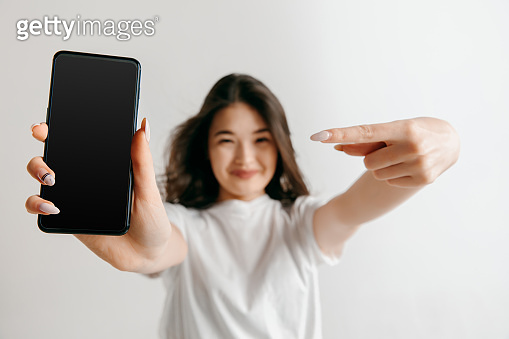 Portrait of a confident casual asian girl showing blank screen of mobile phone