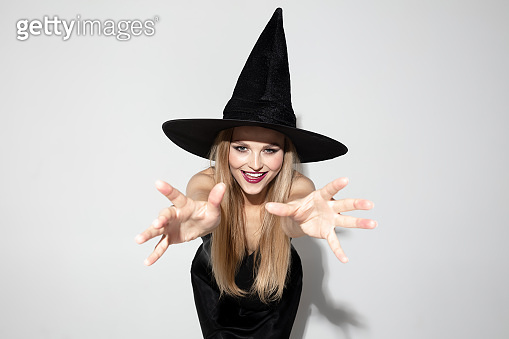 Young woman in hat as a witch on white background